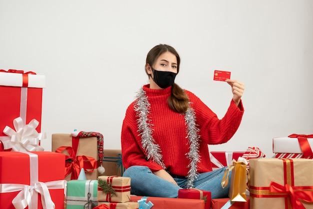Молодая девушка в красном свитере и черной маске с кредитной картой сидит с подарками на белом