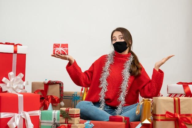 Молодая девушка в красном свитере и черной маске держит подарочную коробку и сидит с подарками на белом