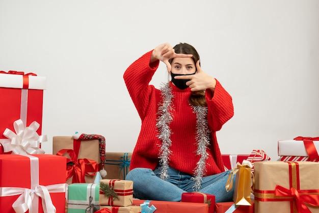 빨간 스웨터와 검은 마스크와 어린 소녀 흰색 선물 주위에 앉아 카메라 기호 만들기