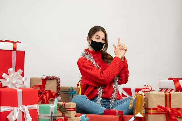 빨간 스웨터와 손으로 총을 만드는 검은 마스크 어린 소녀 흰색 선물 주위에 앉아