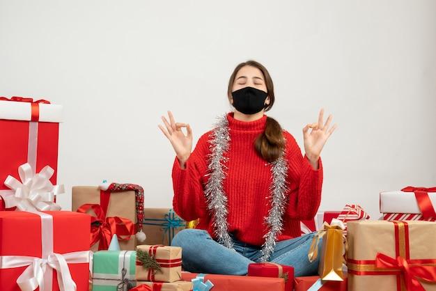 Молодая девушка в красном свитере и черной маске делает знак ок, сидя с подарками на белом