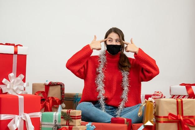 Молодая девушка в красном свитере и черной маске приставляет пальчики к виску, сидя с подарками на белом