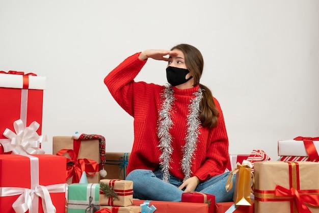 Молодая девушка в красном свитере и черной маске, приложив руку ко лбу, сидит с подарками на белом