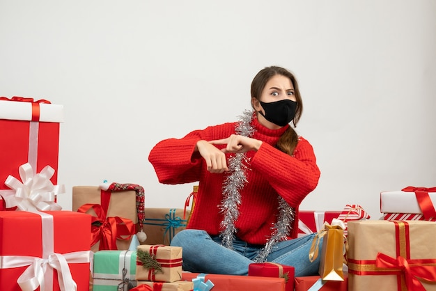 흰색에 검은 마스크와 함께 선물 주위에 앉아 시간을 요구하는 빨간 스웨터와 어린 소녀