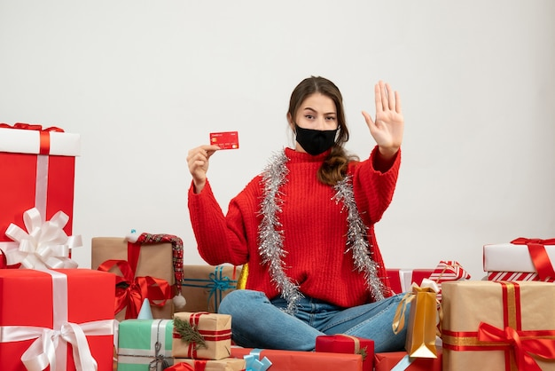 Young girl with red sweater and black mask holding card sitting around presents on white