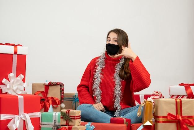 Giovane ragazza con maglione rosso e maschera nera facendo chiamarmi segno di telefono seduto intorno presenta su bianco