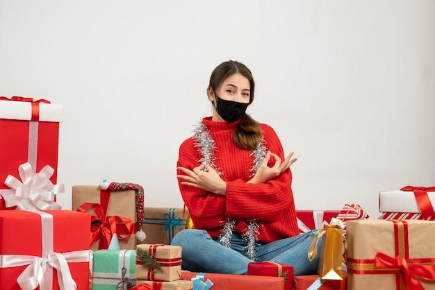 Giovane ragazza con maglione rosso e maschera nera facendo segno okey seduto intorno presenta su bianco
