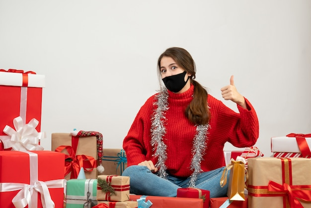 Young girl with red sweater and black mask making thumb up sign sitting around presents on white