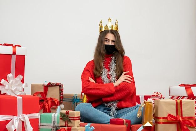 흰색에 검은 마스크 선물 주위에 앉아 빨간 스웨터 횡단 손으로 어린 소녀