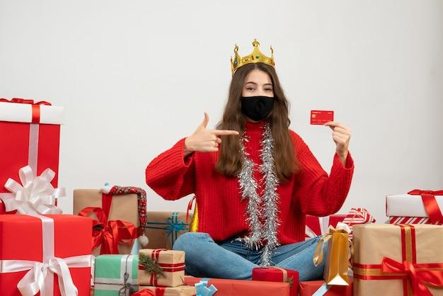 Giovane ragazza con la carta di partecipazione maglione rosso seduto intorno presenta con maschera nera su bianco