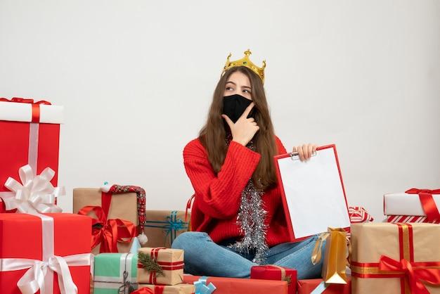 흰색에 검은 마스크와 함께 선물 주위에 앉아 그녀의 턱에 손을 넣어 파일을 들고 빨간 스웨터와 어린 소녀