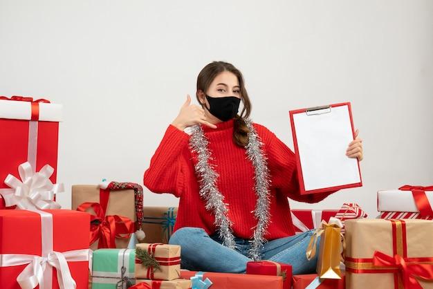 Молодая девушка в красном свитере делает жест по телефону вокруг подарков с черной маской на белом