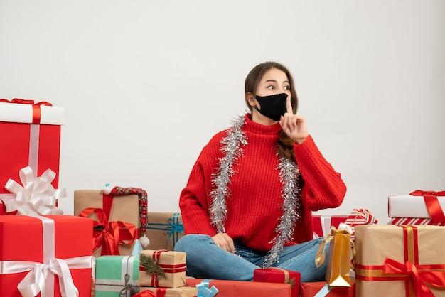 Giovane ragazza con un maglione rosso facendo segno shh seduto intorno presenta su bianco