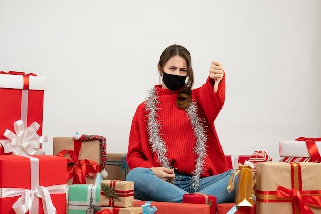 Giovane ragazza con maglione rosso che fa il pollice verso il basso segno seduto intorno presenta con maschera nera su bianco