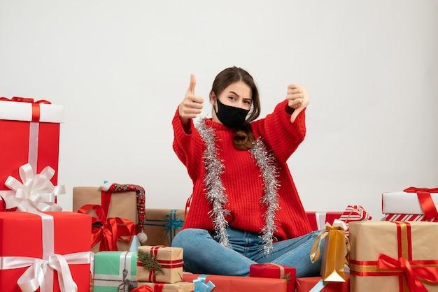 親指を上に、親指を下に向かって座っている赤いセーターを着た少女は、白地に黒のマスクを提示します