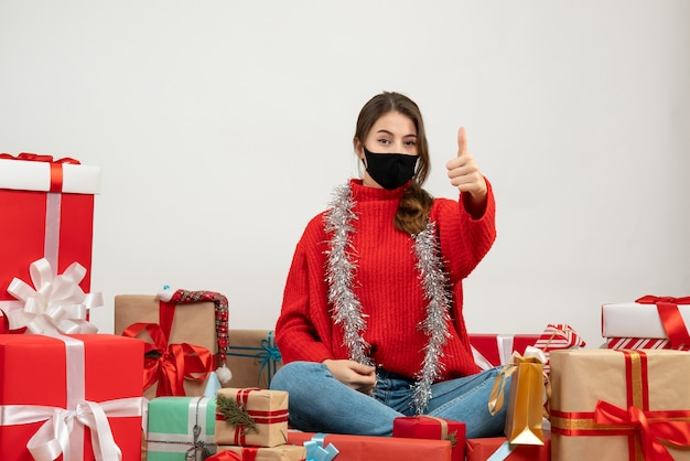 Young girl with red sweater making thumb up sign sitting around presents with black mask on white