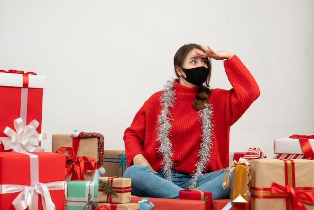 Молодая девушка в красном свитере наблюдает за чем-то сидящим вокруг подарков с черной маской на белом