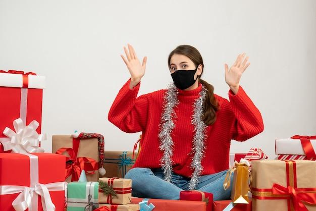 Молодая девушка в красном свитере опускает руки, сидя вокруг подарков на белом