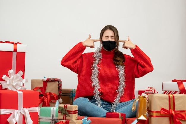 Молодая девушка в красном свитере, приставив пальчиковые пистолеты к виску, сидит с подарками на белом