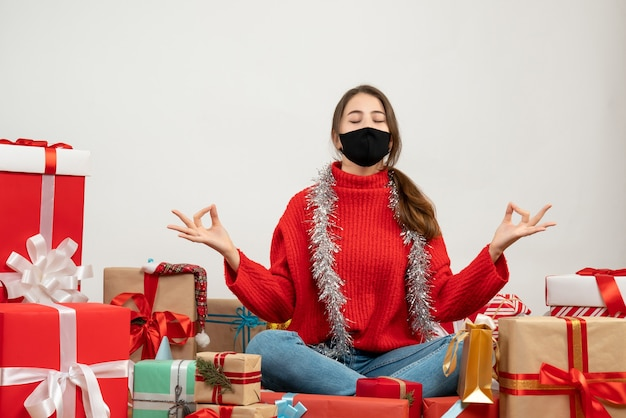 Young girl with red sweater sitting in yoga pose around presents on white