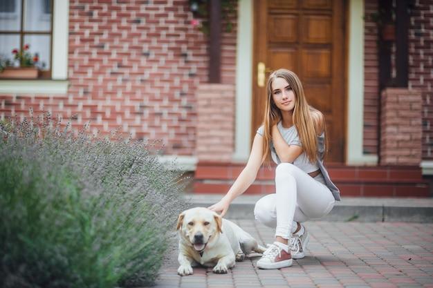 家の前を散歩しているレトリーバーを持つ少女。ラブラドールレトリバーを撫でてカメラを覗き込むスポーツ服を着た魅力的な女性。