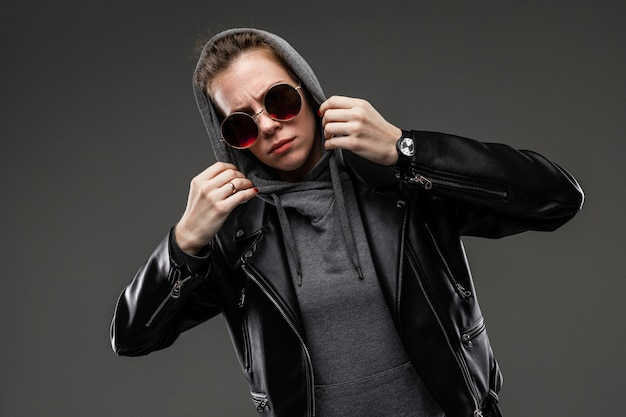 A young girl with rough facial features, patted brown hair, bright manicure, in a grey bike, black jacket, holds sunglasses with her hands, puts a hood on her head and holds it with her hands
