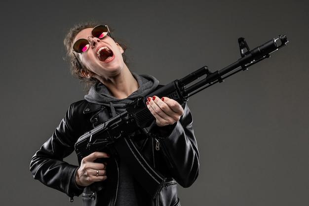 Молодая девушка с грубыми чертами лица, гладкими каштановыми волосами, ярким маникюром, в сером байке, черном пиджаке, с бурными эмоциями держит штурмовую винтовку