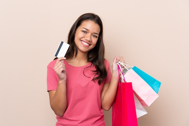 Young girl with shopping bag holding shopping bags and a credit card