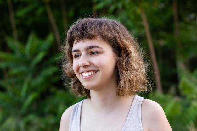 顔の近くの手で笑っている短い巻き毛の少女。外のかなりティーンエイジャーの女の子