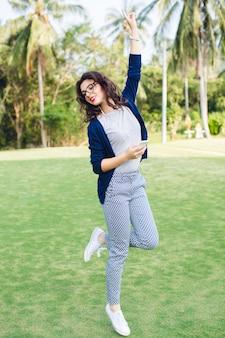 手のひらで公園でジャンプ短い黒髪の少女