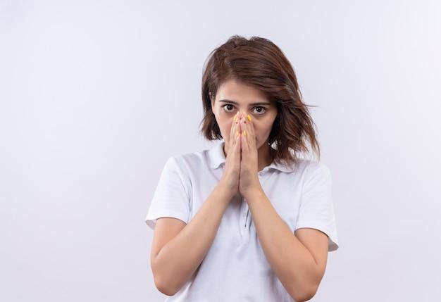 ショックを受けた手で口を覆う白いポロシャツを着た短い髪の少女