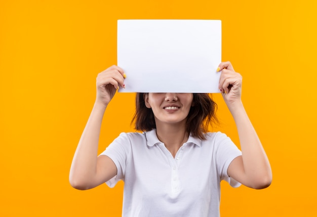 Young girl with short hair wearing white polo shirt hiding eyes beahind blank page smiling cheerfully