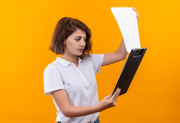Young girl with short hair wearing white polo shirt holding clip board looking at blank pages with serious face
