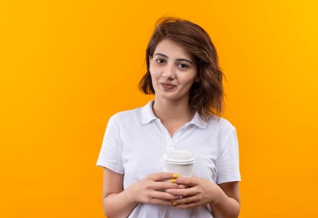 Giovane ragazza con i capelli corti che indossa la maglietta polo bianca tenendo la tazza di caffè guardando la telecamera sorridendo con la faccia felice