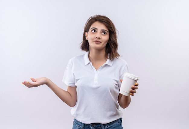 Young girl with short hair wearing white polo shirt holding coffee cup looking confused spreading arm to the side