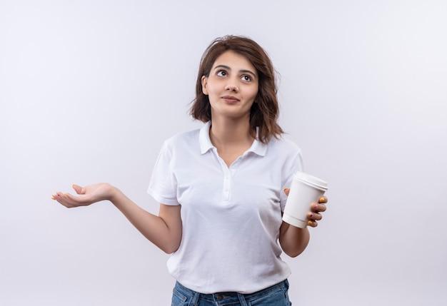 横に腕を広げて混乱しているように見えるコーヒーカップを保持している白いポロシャツを着ている短い髪の少女