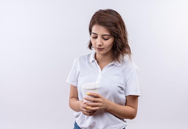 真面目な顔で見下ろしているコーヒーカップを保持している白いポロシャツを着て短い髪の少女