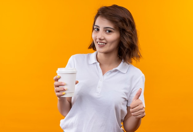 Ragazza con i capelli corti che indossa la camicia di polo bianca che tiene la tazza di caffè che sorride allegra che mostra i pollici in su