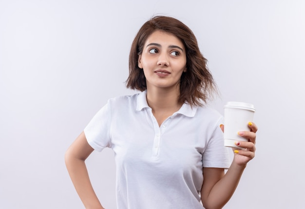 Young girl with short hair wearing white polo shirt holding coffee cup smiling looking aside
