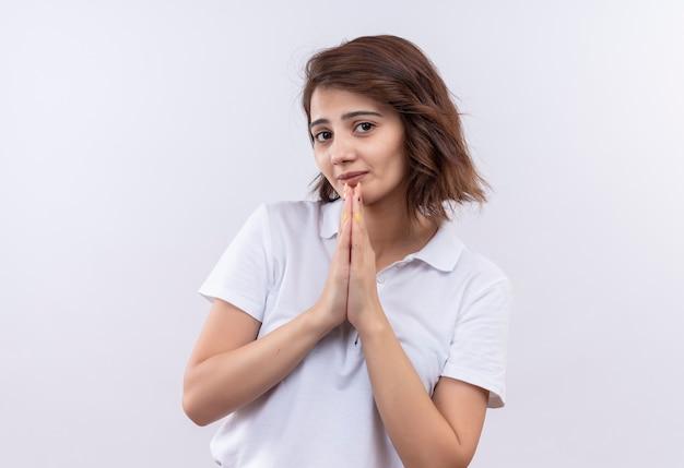Молодая девушка с короткими волосами в белой рубашке поло держится за руки вместе, как молится или просит с выражением надежды