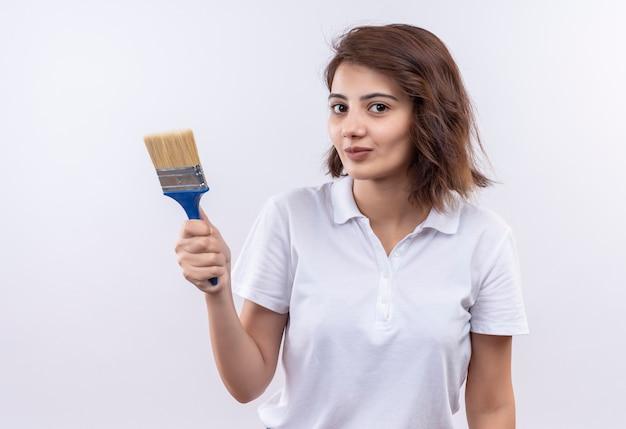 Giovane ragazza con i capelli corti che indossa la maglietta polo bianca tenendo il pennello cercando fiducioso