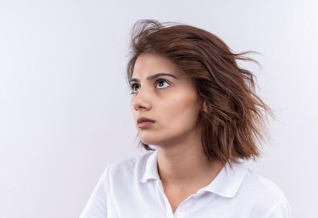 Giovane ragazza con i capelli corti che indossa la maglietta polo bianca che osserva da parte con l'espressione triste sul viso