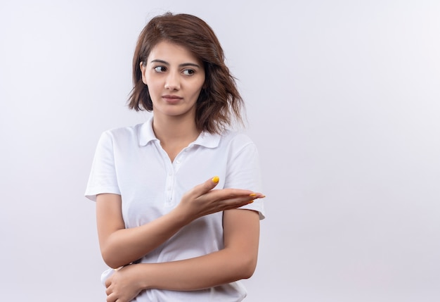 Young girl with short hair wearing white polo shirt looking aside with skeptic expression pointing with arm oh hand to the side