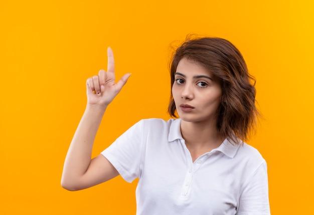 Giovane ragazza con i capelli corti che indossa la maglietta polo bianca che guarda l'obbiettivo con viso serio rivolto con il dito indice in alto