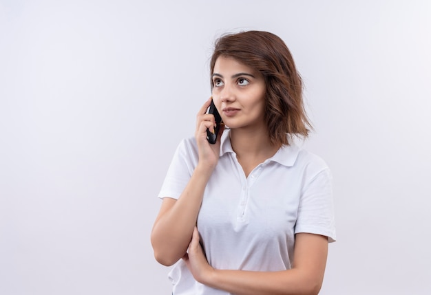 Giovane ragazza con i capelli corti che indossa la maglietta polo bianca cercando fiducioso mentre parla al telefono cellulare