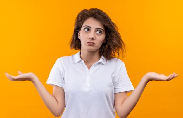 Молодая девушка с короткими волосами в белой рубашке поло выглядит смущенной и неуверенной, разводит руки в стороны, не имея ответа