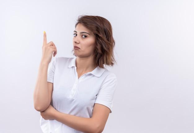 Giovane ragazza con i capelli corti che indossa la maglietta polo bianca che sembra sospetta puntando con il dito indice in alto