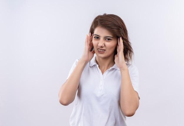 Giovane ragazza con i capelli corti che indossa la maglietta polo bianca cercando stanco rouching testa che soffre di mal di testa