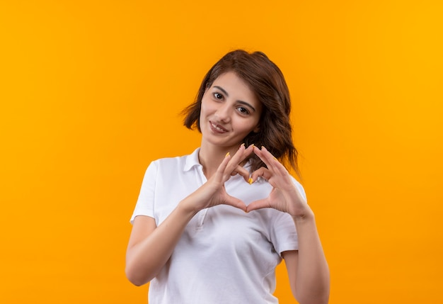 白いポロシャツを着た短い髪の少女が胸に指でハートジェスチャーをして素敵な笑顔