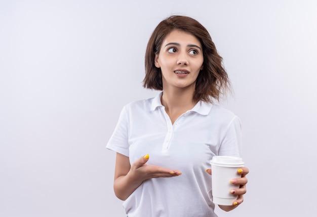 Ragazza con i capelli corti che indossa la maglietta polo bianca che presenta la tazza di caffè che sembra confusa